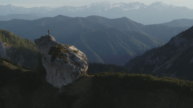aerial drone shot of a female hiker standing on a rocky outcropping surrounded by mountains and forest - explorer stock videos & royalty-free footage
