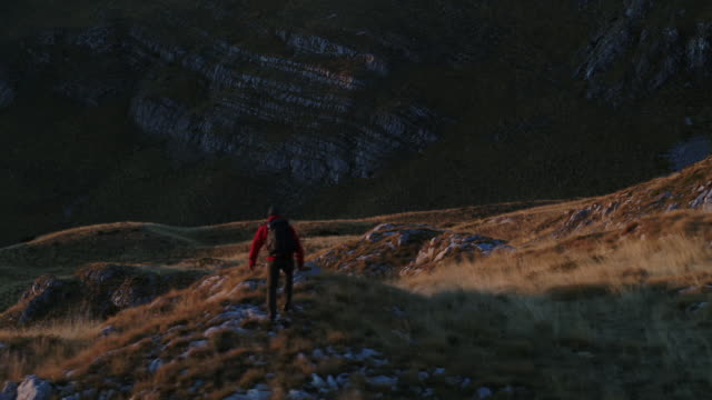 aerial drone shot of a film crew filming a hiker on top of a mountain - durmitor national park stock videos & royalty-free footage