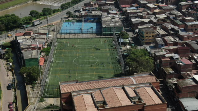 aerial drone shot of a football field in a colombian city - football pitch stock videos & royalty-free footage