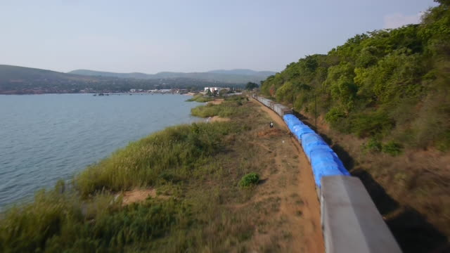 Aerial drone shot of a freight train travelling along the shoreline of Lake Tanganyika.