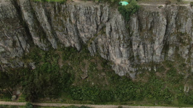 aerial drone shot of a giant cliff face in columbia - rock face stock videos & royalty-free footage