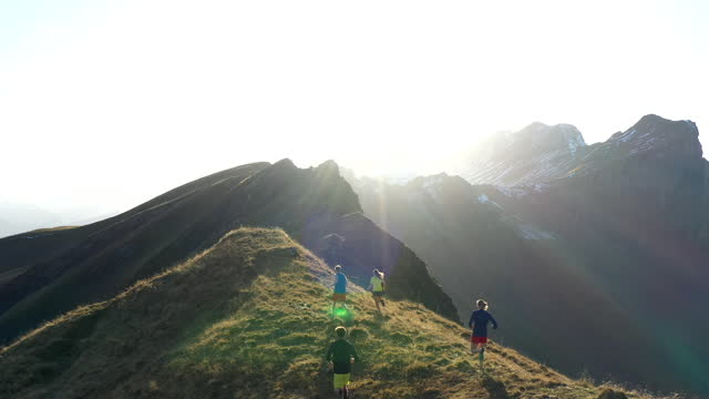 aerial drone shot of a group of trail runners running along a mountain edge with mountains behind - at the edge of stock videos & royalty-free footage