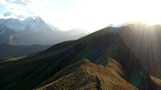 vídeos y material grabado en eventos de stock de disparo aéreo de un grupo de corredores de trail corriendo a lo largo de un borde de la montaña - cuatro personas