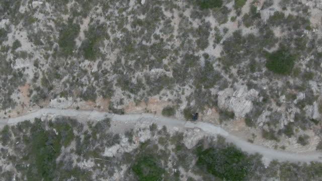 stockvideo's en b-roll-footage met lucht drone shot van een wandelaar langs een pad op een berghelling - alleen oudere mannen