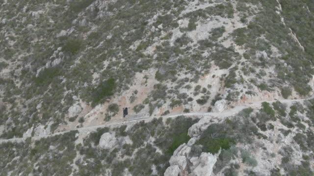 stockvideo's en b-roll-footage met lucht drone schot van een wandelaar die een bergpad afdaalt - alleen oudere mannen