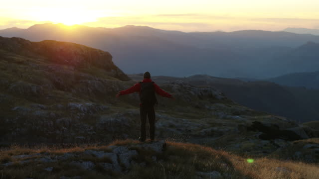aerial drone shot of a hiker standing on the edge of a mountain vista - durmitor national park stock videos & royalty-free footage