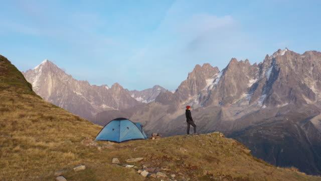 vídeos de stock e filmes b-roll de aerial drone shot of a hiker standing outside a blue tent near mont blanc - tenda estrutura feita pelo homem