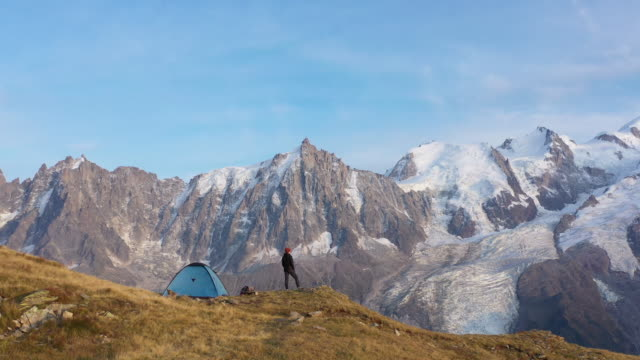 aerial drone shot of a hiker standing outside a blue tent near mont blanc - france stock videos & royalty-free footage