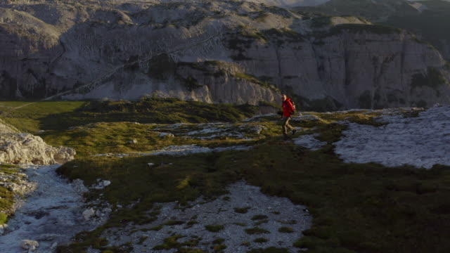 aerial drone shot of a hiker trekking in the grassy foothills of the dolomites - one mid adult man only stock videos & royalty-free footage