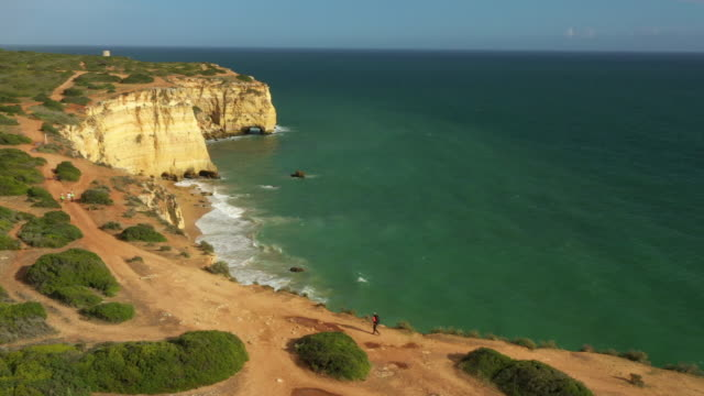 aerial drone shot of a jogger hiking along the ocean bluffs near lisbon - roccia video stock e b–roll