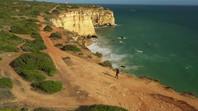 vidéos et rushes de drone aérien tiré d'un jogger randonnée le long de la mer bluffs près de lisbonne - une seule femme d'âge moyen