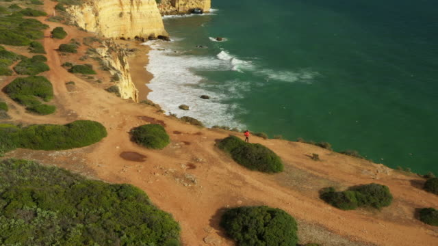 aerial drone shot of a jogger hiking along the ocean bluffs near lisbon - lisbon stock videos & royalty-free footage