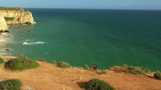 aerial drone shot of a jogger hiking along the ocean bluffs near lisbon - portugal stock videos & royalty-free footage