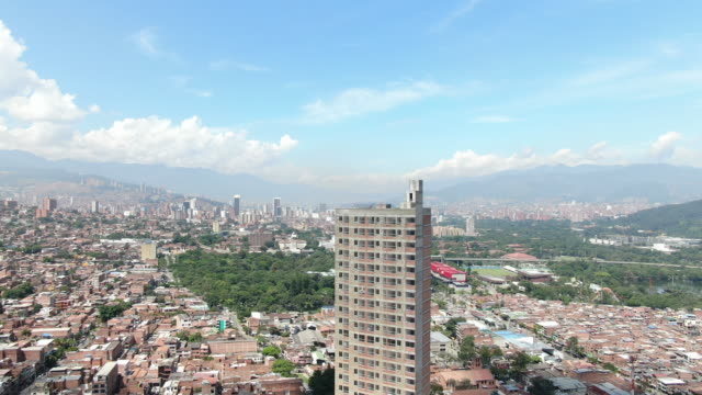 vídeos de stock, filmes e b-roll de o zangão aéreo disparou de uma grande cidade colombiana com edifício alto - mais zoom