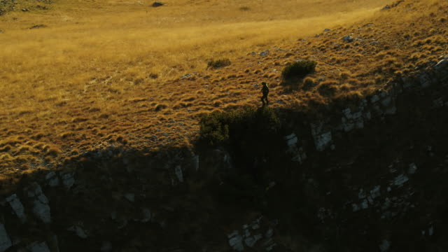 aerial drone shot of a man hiking along a ridgeline in durmitor national park at sunset - distant stock videos & royalty-free footage