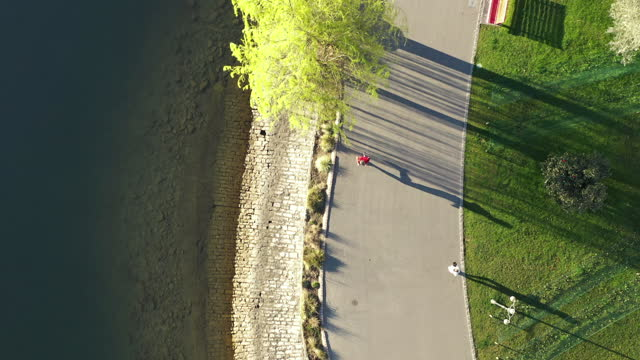aerial drone shot of a man jogging along lake lugano in the morning - jogging stock videos & royalty-free footage