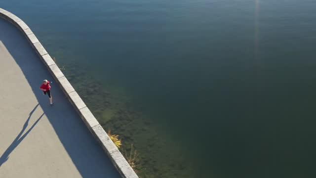 aerial drone shot of a man jogging along lake lugano in the morning - one person stock videos & royalty-free footage
