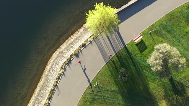 午前中にルガーノ湖に沿ってジョギングしている男の空中ドローンショット - 中年の男性一人点の映像素材/bロール