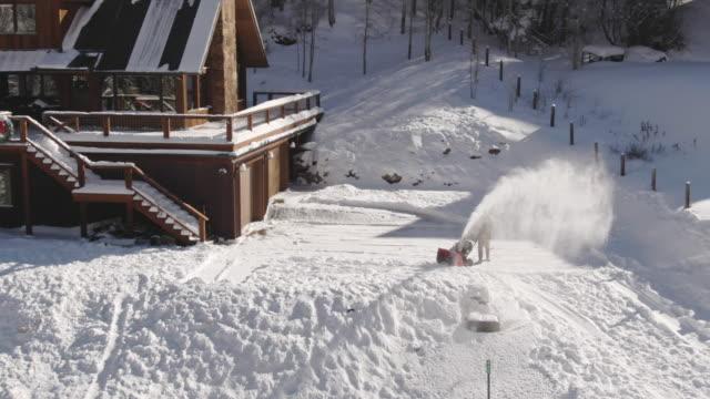 明るい冬の日の雪に覆われたホームの横に吹く男雪の空中ドローン ショット - ユアレイ市点の映像素材/bロール