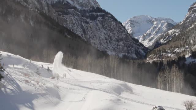 luftbild-drohne schuss von einem mann schnee weht während kinder neben eine verschneite heimat in der san-juan-gebirge (rocky mountains range) schlitten außerhalb ouray, colorado an einem klaren, hellen wintertag - rocky mountains stock-videos und b-roll-filmmaterial