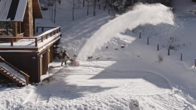 aerial drone shot of a man snowblowing next to a snow-covered home on a bright winter day - rocky mountains north america stock videos & royalty-free footage