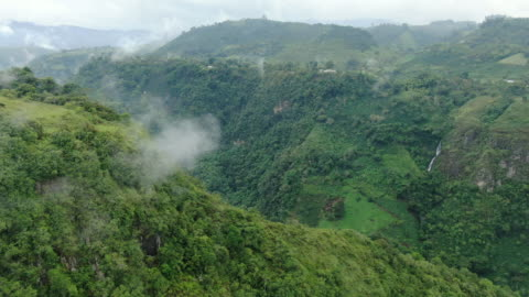 aerial drone shot of a mountain farm and wilderness in colombia - valley stock videos & royalty-free footage
