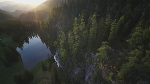 aerial drone shot of a mountain lake surrounded by forest at sunset - natural parkland stock videos & royalty-free footage