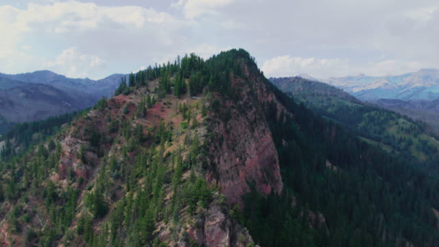 aerial drone shot of a mountain peak in grand teton national park in wyoming on a partly cloudy day - grand teton national park stock videos & royalty-free footage