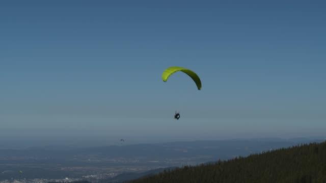 フライブルク付近の森の上のパラグライダーの空中ドローンショット - パラグライディング点の映像素材/bロール