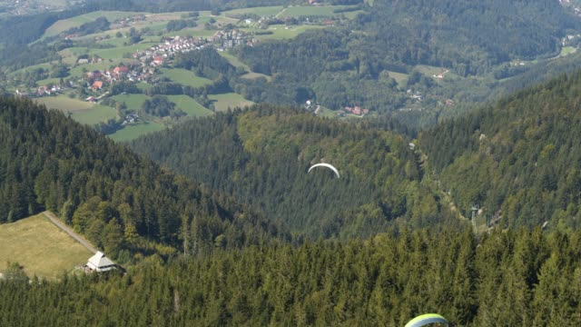 aerial drone shot of a paraglider over a forest near freiburg - paragliding stock videos & royalty-free footage