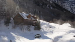 Aerial Drone Shot of a Person Snowblowing in Front of a Picturesque, Snow-Covered Mountain Cabin on a Bright Winter Day