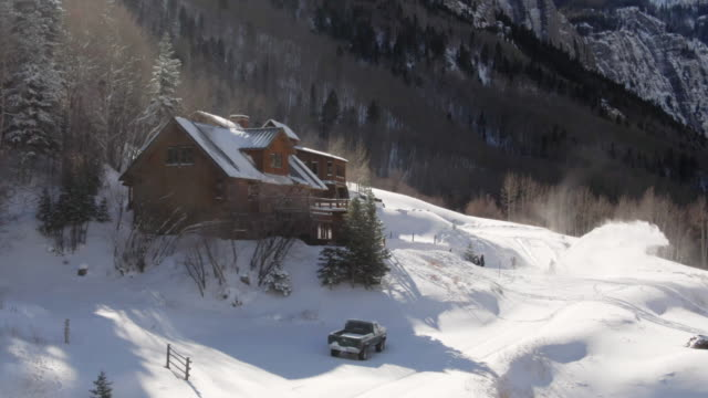 aerial drone shot of a person snowblowing in front of a picturesque, snow-covered mountain cabin on a bright winter day - log cabin stock videos & royalty-free footage