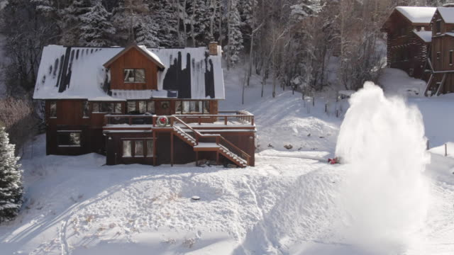 aerial drone shot of a person snowblowing in front of a picturesque, snow-covered mountain cabin with children sledding outside on a bright winter day - log cabin stock videos & royalty-free footage