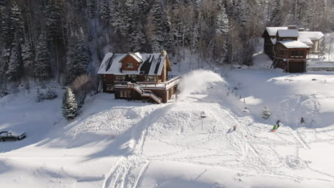 aerial drone shot of a person snowblowing in front of a picturesque, snow-covered mountain home with children sledding outside on a bright winter day - white stock videos & royalty-free footage