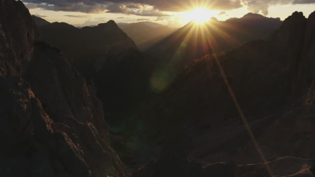 aerial drone shot of a rocky mountain valley at sunset with sun behind - dramatic sky stock videos & royalty-free footage