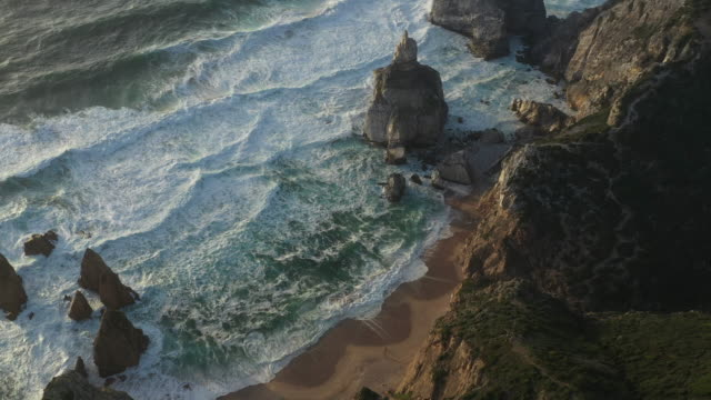 aerial drone shot of a rocky ocean cliffside near lisbon - rocky coastline stock videos & royalty-free footage