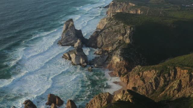vídeos de stock, filmes e b-roll de aerial drone shot of a rocky ocean cliffside near lisbon - coluna de calcário marítimo