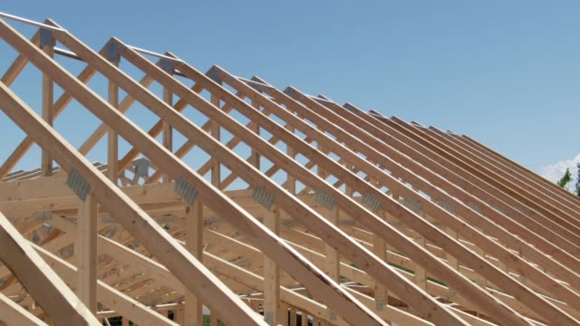 aerial drone shot of a row of wooden roof trusses of a framed house on a construction site on a sunny day - realizzazione video stock e b–roll