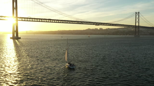 aerial drone shot of a sailboat in a harbor at sunset - segelschiff stock-videos und b-roll-filmmaterial