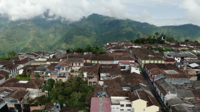 vídeos de stock, filmes e b-roll de o zangão aéreo disparou de uma vila colombiana pequena em um cume - colômbia