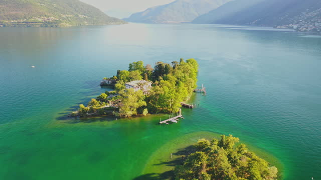 stockvideo's en b-roll-footage met aerial drone shot of a small island in a lake on a sunny day with green blue water - sunny