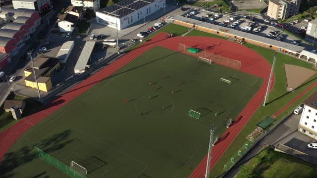 luftdrohne schoss von einem fußballfeld in einer kleinstadt - sportplatz stock-videos und b-roll-filmmaterial