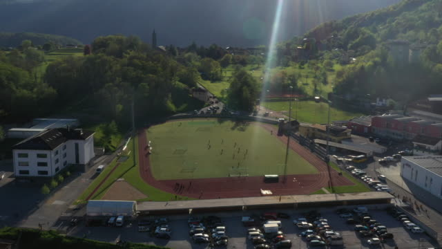 aerial drone shot of a soccer field with people playing - football pitch stock videos and b-roll footage