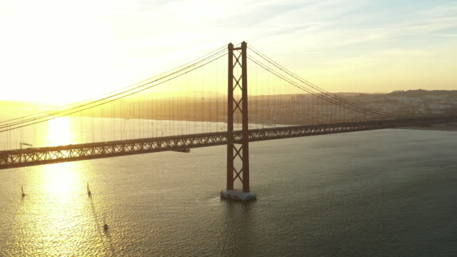 aerial drone shot of a suspension bridge at sunset - lisbon stock videos & royalty-free footage
