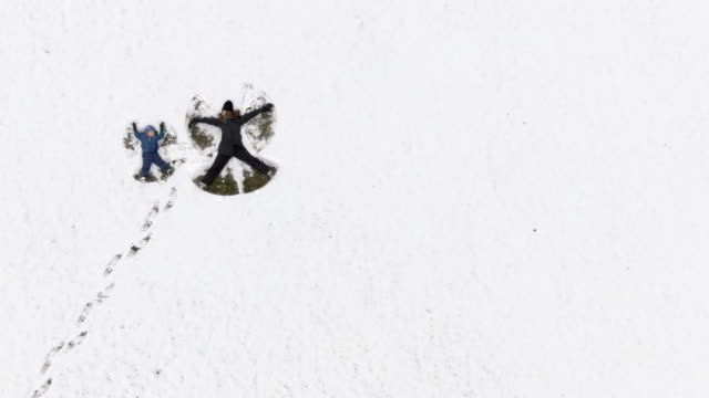 Aerial Drone Shot of a Thirty-Something Mother and Her Three Year-Old Son Making Snow Angels in a Large Snowy Field