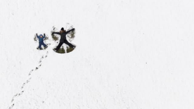 vídeos de stock, filmes e b-roll de drone aerial shot de um trinta-alguma coisa de mãe e filho dela três anos fazendo a neve anjos em um grande campo nevado - 2 3 anos