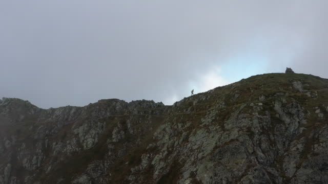 luftdrohne von einem trailrunner an einer bergkante - tal stock-videos und b-roll-filmmaterial