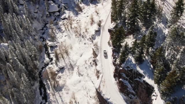 vidéos et rushes de tir de drone aérien d'un camion conduite le long d'une passe de snowy (route) à san juan mountains (montagnes rocheuses) à l'extérieur de ouray, colorado en hiver, entouré d'une forêt d'arbres - mountain range