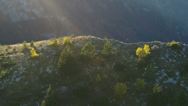 aerial drone shot of a woman walking along a cliff - durmitor national park stock videos & royalty-free footage