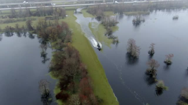 aerial drone shot of an airboat crossing under breaux bridge (interstate 10) near lafayette in the atchafalaya river basin swamp in southern louisiana under an overcast sky - interstate 10 stock videos & royalty-free footage